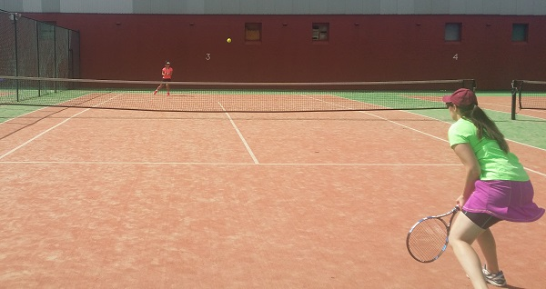 Megan and Barbara playing cross court tennis